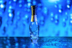 Blue parfume bottle. On the blue background with waterdrops royalty free stock photos