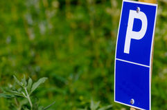 Blue parking sign with a big P on it  green background Stock Photos