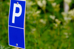 Blue parking sign with a big P on it green background Royalty Free Stock Images
