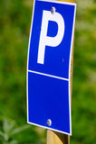 Blue parking sign with a big P on it and green background Royalty Free Stock Images