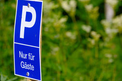 Blue parking sign with a big P on it, green background. only for guests - in German Royalty Free Stock Photos