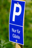 Blue parking sign with a big P on it, green background. only for guests - in German Stock Photography