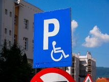 Blue parking sign for disabled persons close up shot. Blue sky with white clouds royalty free stock image