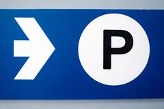 Blue parking sign with white arrow and black capital P on white background stock illustration