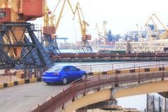 Blue passenger car in the seaport on the background of cranes after unloading. stock image