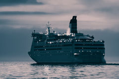 Blue cruise liner. Blue passenger ship sailing in evening in still water. Monochrome Royalty Free Stock Images