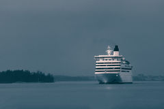 Blue cruise liner. Blue passenger ship sailing in evening in still water. Monochrome Stock Image