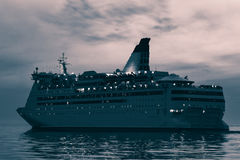 Blue cruise liner. Blue passenger ship sailing in evening in still water. Monochrome Royalty Free Stock Photos