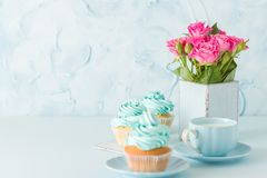 Blue pastel horisontal banner with decorated cupcakes, cup of coffe with milk and bouquet of pink roses. Blue pastel banner with decorated cupcakes, cup of royalty free stock photos