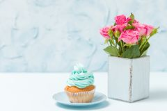 Blue pastel horizontal banner with cupcake with blue decoration and bouquet of pink roses in retro shabby chic vase. Blue pastel horizontal banner with cupcake Royalty Free Stock Photo