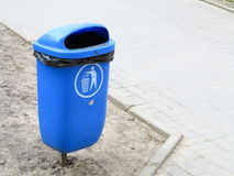 Blue pastic garbage bin or can on street. Blue pastic garbage bin or can and bench on street Royalty Free Stock Photography