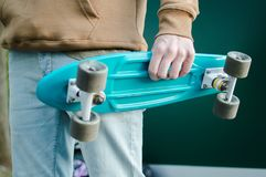 Penny skateboard commute hipster transport solutions. Blue pastic penny skateboard in the hand of the young modern man weared in brown hoodie and blue jeans Royalty Free Stock Images