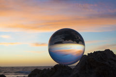 blue patches and peach sky Sun and crystal ball at sunset Stock Images