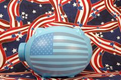 Blue patriotic piggy bank. Blue ceramic piggy bank with American flag on side and background of stars and stripes. Good for national American holidays Royalty Free Stock Photo