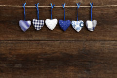 Blue pattern Gingham Love Valentine's hearts hanging on wooden t. Blue Gingham Love Valentine's hearts natural cord and blue clips hanging on rustic driftwood Stock Image
