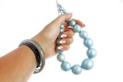 Blue pearls Woman hand holding on isolated white cutout background. Studio photo with studio lighting easy to use for. Blue pearl necklace Woman hand holding on royalty free stock photo