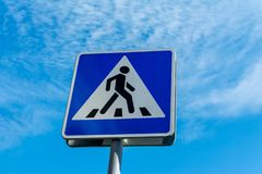 Blue pedestrian crossing sign close up against a cloudy sky royalty free stock photos
