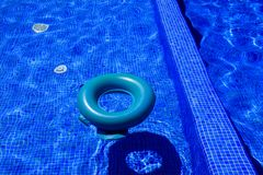 Blue peldridge for kids at swimming pool. Blue peldridge for kids at outdoor swimming pool. Reflection on water Royalty Free Stock Photo