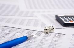Blue pen, calculator and dice Stock Photos