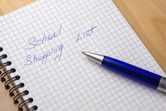 Blue pen on a notebook with sheets in a cage. Sign - school shopping list.  royalty free stock photo