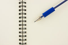 Blue pen on recycled notebook Royalty Free Stock Photography
