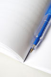 Blue pen on white open book Royalty Free Stock Images