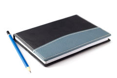 Blue pencil on black leather moleskin notebook Royalty Free Stock Images