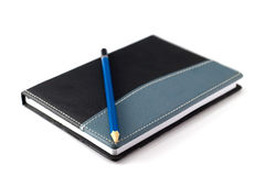 Blue pencil on black leather moleskin notebook Royalty Free Stock Photos