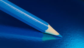 Blue pencil on a blue background Stock Photo