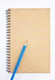 Blue pencil on brown notebook's cover. Royalty Free Stock Images