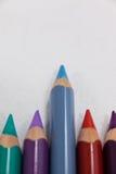 Blue pencil che sta fuori da una fila delle matite colorate Fotografie Stock Libere da Diritti