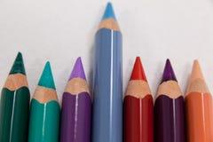 Blue pencil che sta fuori da una fila delle matite colorate Immagini Stock Libere da Diritti