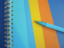 Blue pencil on the colorful spiral notebook Royalty Free Stock Photography