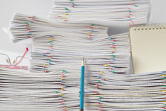 Blue pencil in front of pile of overload paperwork Stock Photos