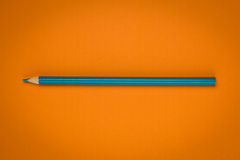 Blue pencil on orange paper Stock Photography
