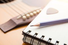 Blue pencil put on the book. Notebook put on guitar royalty free stock photos
