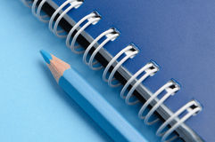 Blue pencil and spiral of notebook Royalty Free Stock Photos