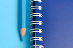 Blue pencil and spiral of notebook Stock Image