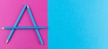 Blue pencils安排了作为在紫色和蓝色对比背景的信件A 免版税库存图片