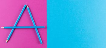 Blue pencils arranged as letter A on purple and blue contrast background. Blue pencils arranged as letter A on purple and blue contrast background Royalty Free Stock Images
