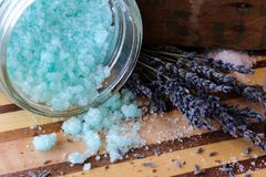 Blue bath salts and lavender flowers. Blue peppermint and eucalyptus bath salts on a beautiful wood board with dried lavender flowers. Image for spa, body care Royalty Free Stock Photo