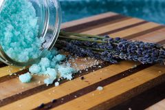 Blue bath salts and lavender. Blue peppermint and eucalyptus bath salts on a beautiful wood board with dried lavender flowers. Image for spa, body care, relaxing Stock Images