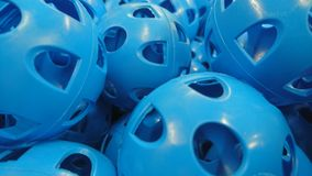 Blue Perforated Plastic Sports Balls. Pe activity golf cricket air wind holes box collection pile group mountain close up focus blur layers bag round sitting Royalty Free Stock Photo