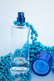 Blue Perfume Bottle. A blue perfume bottle decorated with a necklace of blue beads stock photography