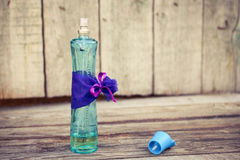 Blue perfume bottle on the wooden background. Toned image Royalty Free Stock Photography