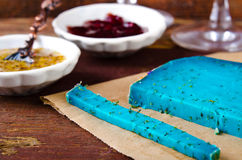 Blue pesto cheese with herbs, pomegranate jam and sauces on wooden rustic background Royalty Free Stock Photography