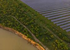 Blue Photovoltaic Solar Panels. Photovoltaic solar panels for renewable energy, near a river Royalty Free Stock Photos