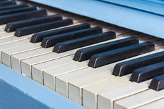Blue piano close-up with black and white keys Royalty Free Stock Photography