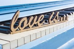 Blue piano close-up with black and white keys with text Love is Stock Image