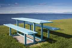 Blue Picnic Table by the Sea. Garish blue picnic table by the sea looking out towards the island of Arran in Scotland, UK Stock Photo